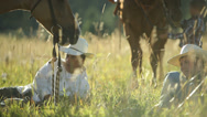 Stock Video Footage of Cowboys sit in grass taking break