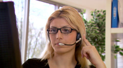 Attractive female customer service operater assisting customers in a call Stock Footage