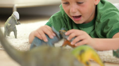 Young boy playing with toy dinosaurs - stock footage
