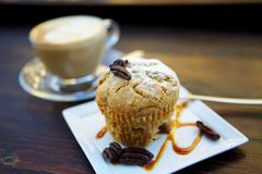 A muffin with pecan nuts and a cup of cappuccino - stock photo