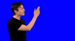 Television presenter or weatherman does piece to camera against bluescreen Stock Footage