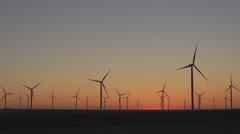 Turbine group windmill energy twilight sunset orange landscape field production  Stock Footage