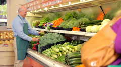 Produce worker stocking grocery store shelves Stock Footage