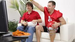 Group of friends watching sports on TV and cheering - stock footage