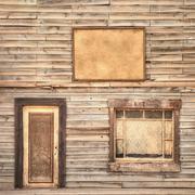 western vintage wooden facade background. door, window and blank board - stock photo