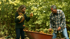 Mature couple playing with leaves in the Fall. Slow motion. Stock Footage