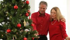 Mature couple decorating tree at Christmas Stock Footage