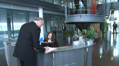 Business group and receptionist in a large contemporary office building. High Stock Footage