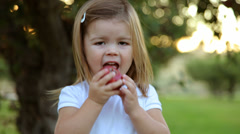 Young girl in orchard take bite of apple - stock footage