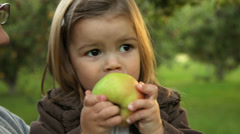 Mother and young daughter share an apple - stock footage