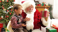 Santa Claus gives Christmas gift to young boy Stock Footage