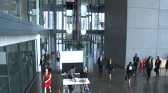 Camera crane in large corporate building atrium and multiple employees at a Stock Footage