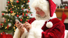 Santa Claus talking on cell phone at Christmas Stock Footage