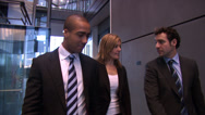 Stock Video Footage of Group of businessmen and women talking as they move through grand financial