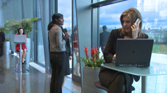 Business group with woman on laptop and mobile cell phone in busy modern office Stock Footage