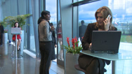 Stock Video Footage of Business group with woman on laptop and mobile cell phone in busy modern office
