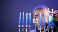 Young boy lights menorah Stock Footage