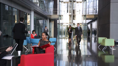 Large multi ethnic business group in relaxed meeting area of a large Stock Footage