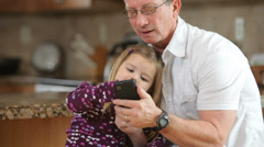 Grandfather and granddaughter with cell phone Stock Footage