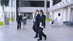 Steadicam dolly back through office following large group of business people.  - stock footage