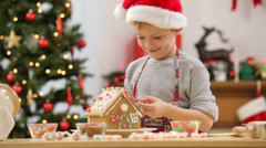 Young boy making Christmas gingerbread house Stock Footage