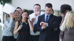 Successful Businessman with his entourage of staff vying for his attention. A Stock Footage