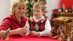 Mother helps son set up Christmas nativity scene - stock footage
