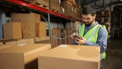 Man in shipping warehouse scans labels on boxes Stock Footage