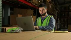 Business man in warehouse with laptop on cardboard box Stock Footage