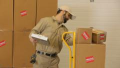Delivery man delivers packages through warehouse - stock footage