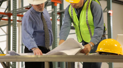 Two industrial contractors looking over blue prints and construction progress - stock footage