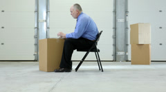 Business man in warehouse with laptop on cardboard box - stock footage