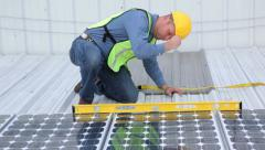 Stock Video Footage of Contractor installing solar panels on industrial rooftop, portrait