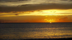 The setting sun vanishes behind the horizon, leaving behind golden skies over a  Stock Footage