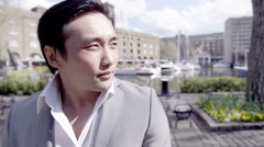 Portrait of a young handsome Asian man outdoors in the city - stock footage