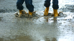 Two young boys jumping in mud puddle Stock Footage