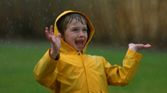 Young boy playing in rain, slow motion Stock Footage