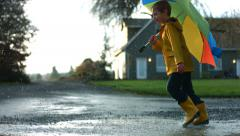 Young boy running through puddles with umbrella, slow motion Stock Footage