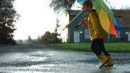 Stock Video Footage of Young boy running through puddles with umbrella, slow motion