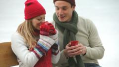 Couple drinking hot beverages at ice skating rink Stock Footage