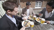 Stock Video Footage of Young attractive male friends outdoors celebrating with drinks and lunch. Could