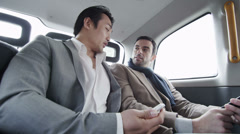 Business people riding in the back of a taxi Stock Footage