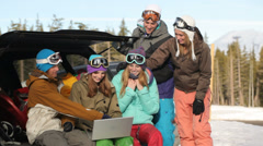 Group of young snowboarders on the slopes using laptop - stock footage