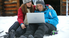 Couple using a laptop in the snow Stock Footage