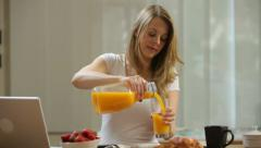 Woman having breakfast and using laptop computer - stock footage