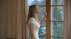 Couple look out window together in morning - stock footage