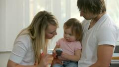 Family with young child talking on cell phone together Stock Footage