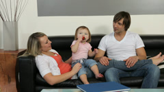 Family with young child hanging out in living room Stock Footage