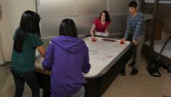 Group of young people play air hockey together Stock Footage