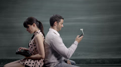 Couple against blackboard send text messages and emails.  People playing with Stock Footage